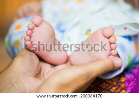 Baby feet cupped into mothers hands.
