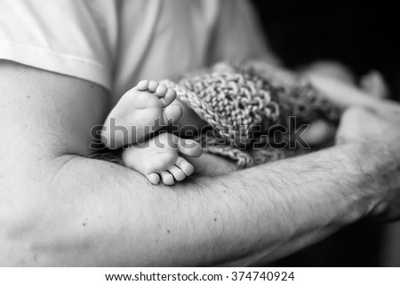 Baby feet in father hands. Black-and-white photo. Baby's feet in black and white