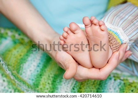 Baby feet in father hands. Tiny Newborn Baby's feet on male shaped hands closeup. Dad and his Child. Happy Family concept. - stock photo