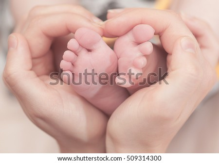 Baby feet in mother hands. Feet on female heart shaped hands closeup. Happy family concept. Mom and her child.