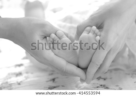 baby feet in mother hands. Happy Family concept. Tiny Newborn Baby's feet on female hand. Heart Shaped hands close up. Mom and her Child. - stock photo