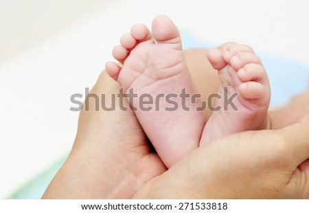 Baby Feet in Mother Hands. New Born Kid Foot, Family Lovely Concept