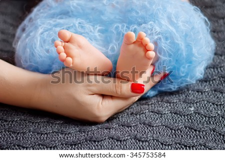 Baby feet in mother hands. Tiny Newborn Baby's feet on female Shaped hands closeup. Mom and her Child. Happy Family concept. Beautiful conceptual image of Maternity - stock photo