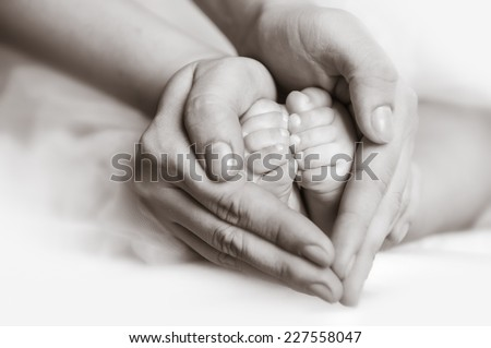 Baby feet in mother's hands. Mother's hands carefully keeping baby's foot with tenderness