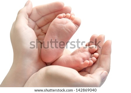 Baby feet in mother's hands on a white background