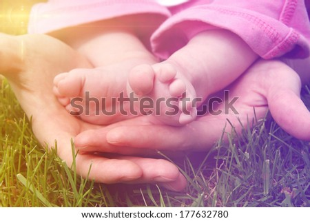 Baby feet in mother's hands outside in grass - stock photo