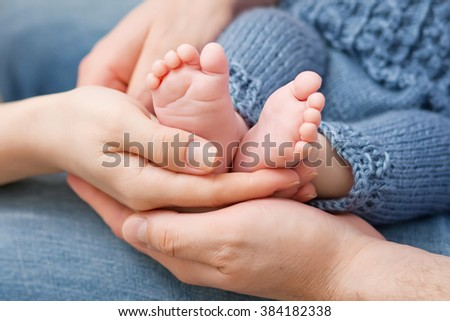Baby feet in parents hands. Tiny Newborn Baby's feet on parents shaped hands closeup. Parents and they Child. Happy Family concept. - stock photo