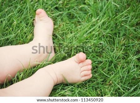 Baby feet in the grass - stock photo