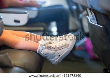 Baby feet on seat in the aircraft - stock photo