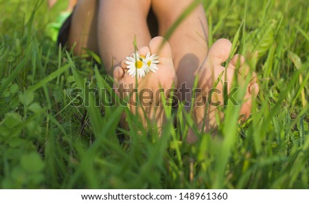 Baby feet on the grass. - stock photo