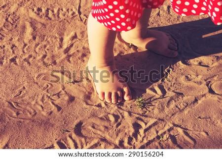 Baby feet walking on sand beach at sunset. Toned - stock photo