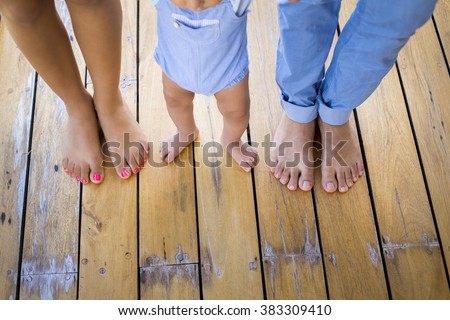 Baby firsts steps holding his parents hands - stock photo