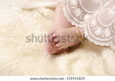 Baby fit with gold chain. Ceremonial clothes. - stock photo