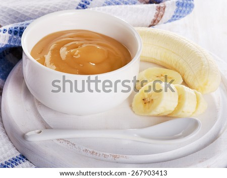 Baby food - bananas puree in a white bowl. Selective focus