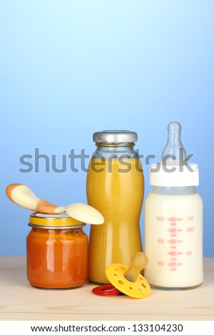 Baby food, bottle of milk, puree and juice on blue background - stock photo