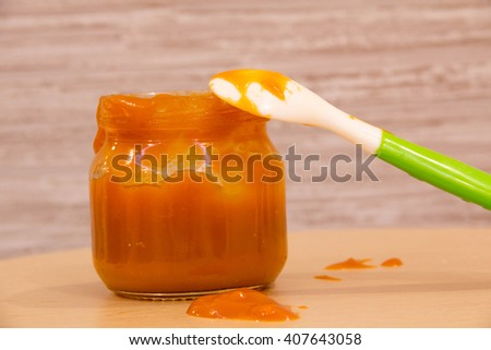 Baby food puree carrots in a glass bottle with a spoon on the table amid. Selective focus. - stock photo