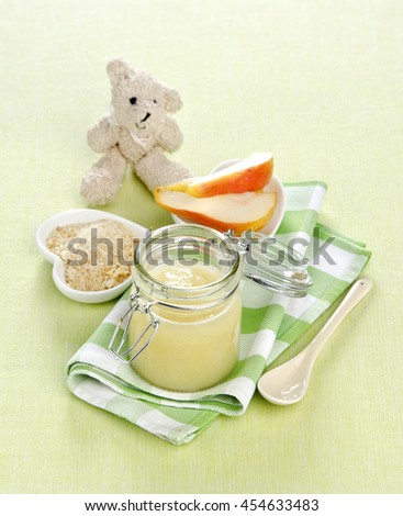 baby food puree of pear fruit in a bank with a toy bear near