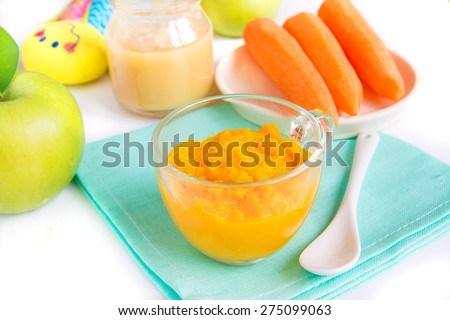 Baby food (pureed carrot and apple) close up on white table