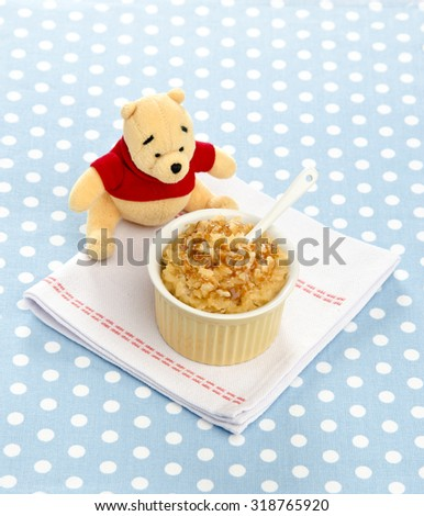 baby food rice with honey in a bowl of ceramic toy bear next to a blue polka-dot tablecloth - stock photo