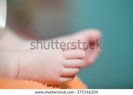 Baby foot close up. Baby foot and toes on a bed. Baby two months from birth. - stock photo
