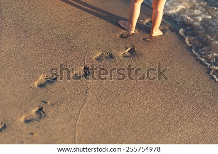 baby footprints in the sand - stock photo