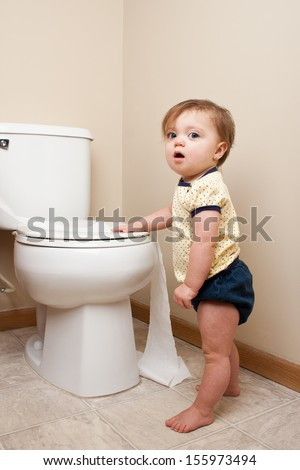 Baby getting caught getting into toilet paper - stock photo