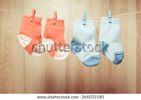 Baby girl and boy socks attached to the rope - stock photo