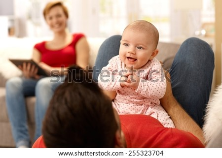 Baby girl and father playing on sofa, mother watching from background. - stock photo