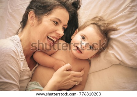 Baby girl and  her mother lying in bed. Space for copy.