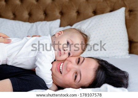 Baby girl and her mother lying on the bed - stock photo