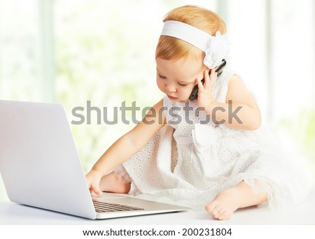 baby girl at a laptop computer, mobile phone - stock photo