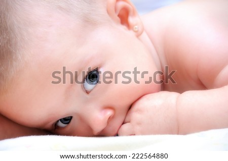 Baby girl bites the hand on the bed - stock photo