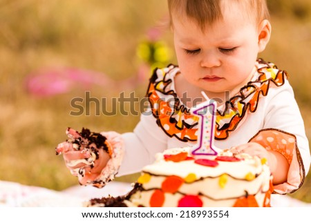Baby girl celebrating her first bithday with gourmet cake and balloons. - stock photo