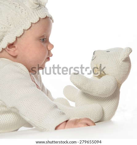 baby girl child lying down on white blanket  fashion portrait  studio shot isolated on white caucasian playing with white teddy bear in hat - stock photo
