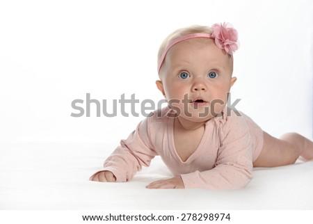 baby girl child lying down on white blanket  pink fashion portrait face studio shot isolated on white caucasian - stock photo