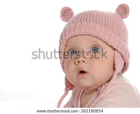 baby girl child lying down on white blanket  pink fashion portrait face studio shot isolated on white caucasian warm hat - stock photo