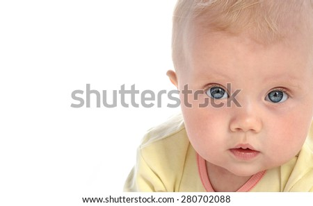 baby girl child lying down on white blanket  portrait face studio shot isolated on white caucasian looking at camera blue eyes - stock photo