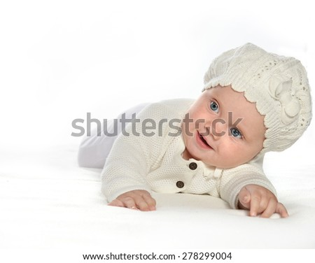 baby girl child lying down on white blanket smiling happy  fashion portrait face studio shot isolated on white caucasian  hat warm cloting - stock photo