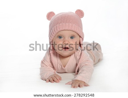baby girl child lying down on white blanket smiling happy pink fashion portrait face studio shot isolated on white caucasian - stock photo