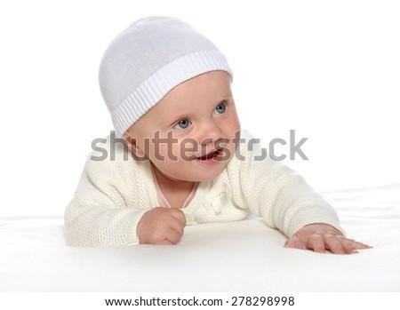baby girl child lying down on white blanket smiling happy white clothing hat fashion portrait face studio shot isolated on white caucasian - stock photo