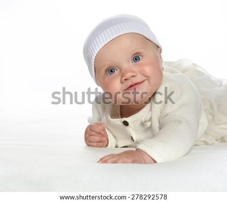 baby girl child lying down on white blanket smiling happy white dress fashion portrait face studio shot isolated on white caucasian - stock photo