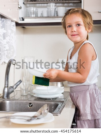 Baby girl cleaning dirty dishes at domestic kitchen
