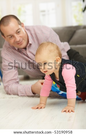Baby girl crawling on floor, dad watching in background smiling.