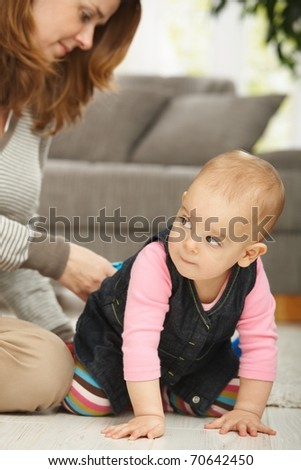 Baby girl crawling on floor with mum sitting in the background.? - stock photo