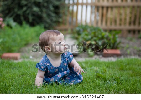 Baby girl crawling on the grass, selective focus