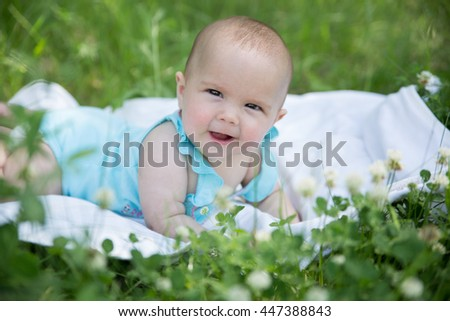 Baby girl crawling on the grass. Selective focus on her eyes