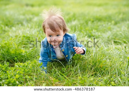 Baby girl crawling on the green grass outdoors in summer