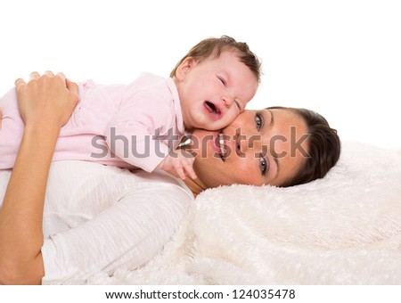 Baby girl crying and mother lying together on white fur blanket - stock photo