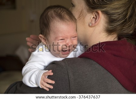 baby girl crying on mums shoulder