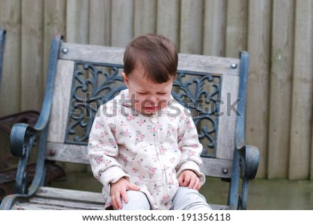 Baby girl crying sitting on a chair in the garden   - stock photo